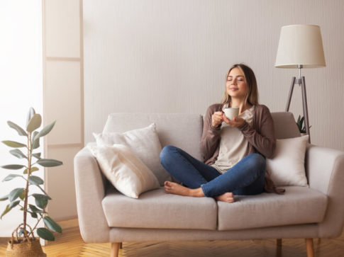 woman-relaxing-at-home-with-a-cup-coffee-on-her-hand